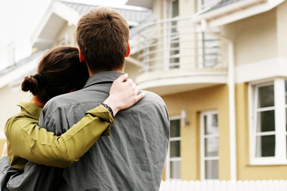 obejmująca się para patrząca na dom